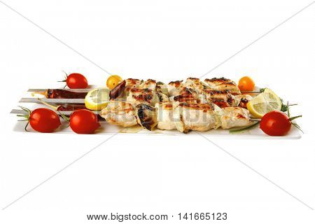 shish kebab on white platter with vegetables