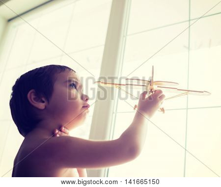 Happy kid playing with toy airplane on home window
