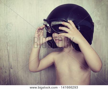 Happy playful little boy with flying helmet