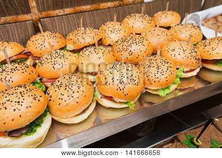 Catering american style - served table with plenty of hamburgers ready for guests. Snack at event, lots of fast food.