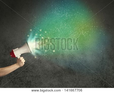 Caucasian business hand holding megaphone with white sparkles on a grunge background