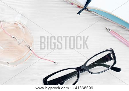 Young modern woman workplace. Eyeglasses, perfume, pen and notebook on white wooden background, copyspace