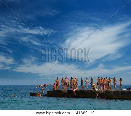ODESSA UKRAINE - JULY 30 2016: People jumping from the pier at the 'Golden Coast' beach in Odessa Ukraine