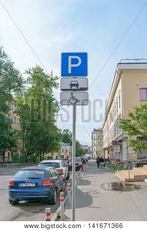 Moscow, Russia - July 07, 2016: Road sign indicating the parking space for the invalid passenger cars near the building of the Russian Economic University of Plekhanov