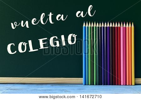 text vuelta al colegio, back to school in spanish written in a chalkboard and some new pencil crayons of different colors put in line, on a blue wooden desk