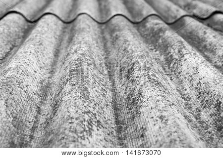 the abstract textured background a closeup of old wavy asbestos-cement slate of monochrome tone