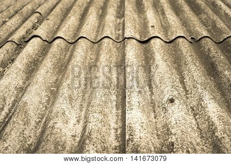 the abstract textured background a closeup of old wavy asbestos-cement slate of tone sepia