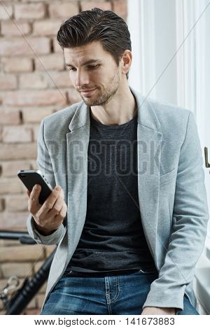 Casual young man holding mobile, thinking.