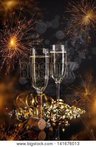 Champagne glasses on festive sparkler background, New Year concept