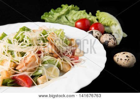Caesar salad with prawns cherry tomato and cheese on white plate on black background