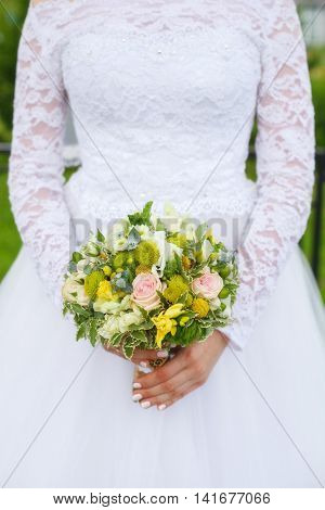 Beautiful green wedding bouquet in bride's hands closeup selective focus