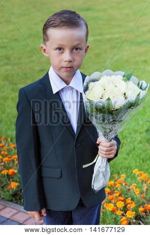 Outdoor portrait of nice little boy first-grader with a bouquet of white chrysanthemums
