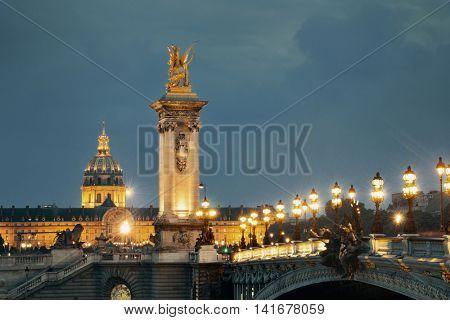Alexandre III bridge night view with Napoleon's tomb in Paris, France.