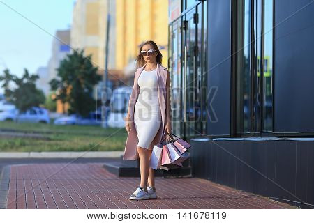 Fashion Shopping Girl Portrait. Beautiful girl in sunglasses. After day shopping. Girl with shopping bags. Shopper. Sales.