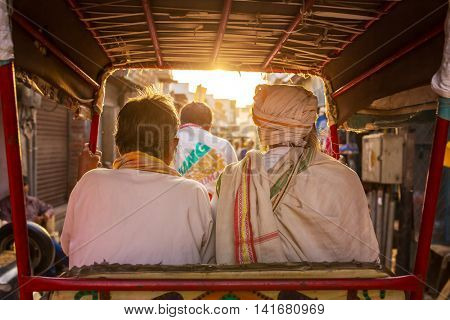 Vrindavan, India - March 16, 2016: Two unidentified men riding on rickshaw in the sunny morning in Vrindavan, India