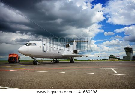 Refueling an airplane at the small russian airport against blue cloudy sky. Soft selective focus and shallow depth of field