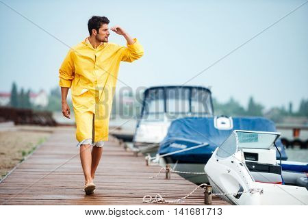 Young handsome sailor man in yellow cloak walking at the sea pier and looking at something