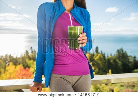 Healthy lifestyle clean eating person holding glass of fresh blended spinach leafy greens drinking smoothie as part of a health diet for a fitness active life. Morning breakfast outdoor nature.