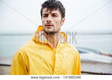 Close up portrait of a handsome young sailor man in yellow cloak