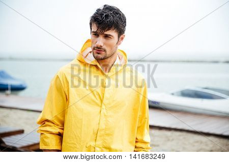 Portrait of a sailor man in yellow cloak at the pier