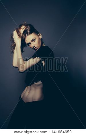 Young girl with brown hair serious face in black suit with bare thin and slim belly posing with her hand near head posing on dark background studio