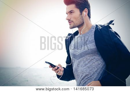 Portrait of a young sports man running with headphones