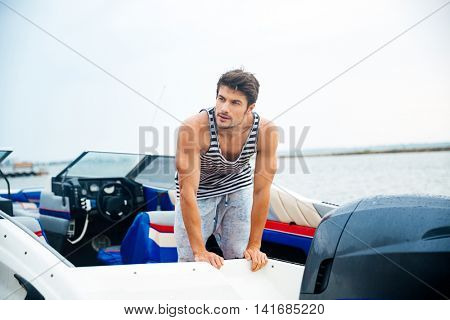 Young sailor man in his motor boat