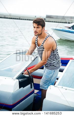 Young handsome bearded sailor man driving his motor boat