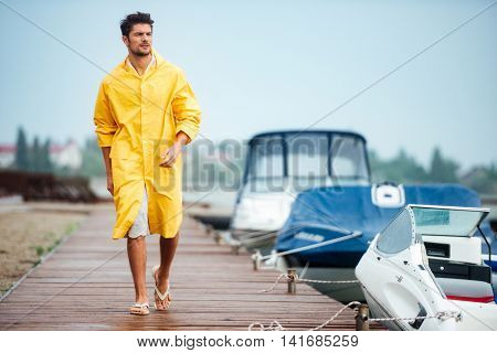 Young handsome sailor man in yellow cloak walking at the sea pier