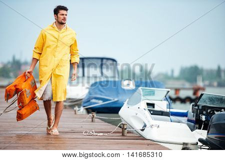 Young handsome sailor man in yellow cloak walking at the sea pier holding life vest
