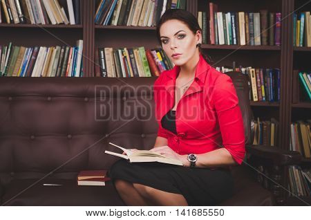 Attractive Business Woman In A Business Suit Sitting On A Leather Brown Sofa In The Office And Readi