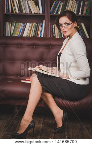 Attractive Business Woman In A Business Suit With Glasses Sittin