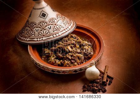 tajine with meat, onion, dried grape and cinnamon