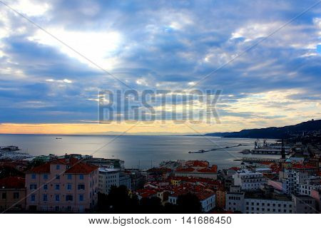 A landscape of Trieste city in Italy with sea and port view at a sunset with