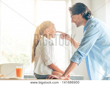 Cute little girl and her handsome father are talking and smiling while sitting in kitchen at home. Dad is touching his daughter's nose