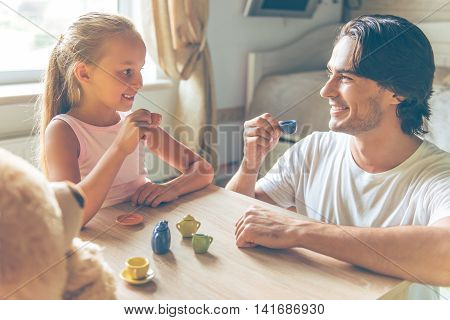 Cute little girl and her handsome father are holding little toy cups looking at each other and smiling while playing at home