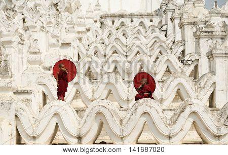 BurmaThe Novice monk holding red umbrella on the pagoda
