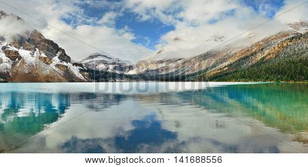 Bow Lake panorama reflection with snow capped mountain and forest in Banff National Park