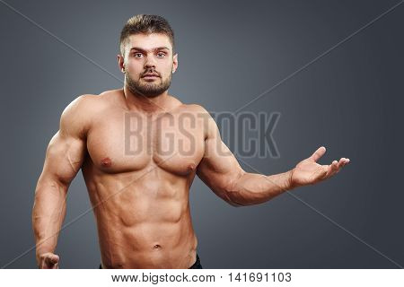 Muscular shirtless young man confused and shrug. Bodybuilder asking with hands and facial expression. Athlete hard choice with copy space.