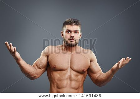 Muscular shirtless young man unsure or confused. Bodybuilder asking with hands and facial expression. Athlete hard choice.