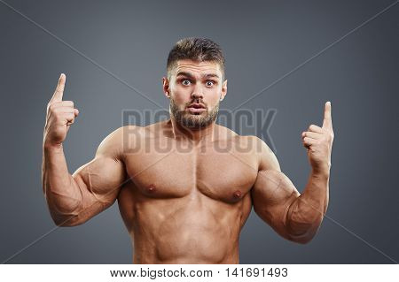 Shocked strong man pointing fingers upwards over grey background. Healthy bodybuilder surprised showing to the top copy space.