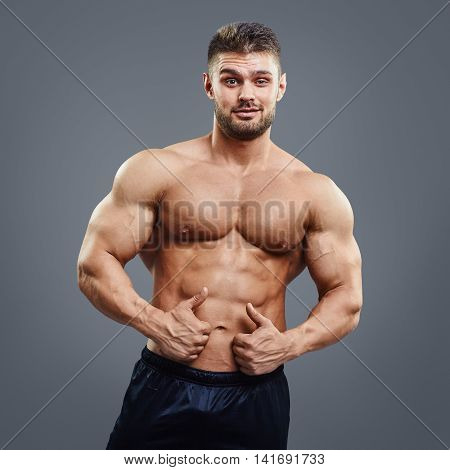 Muscular man is looking at the camera and showing thumbs up sign on grey background. Fitness trainer showing thumbs up gesture.