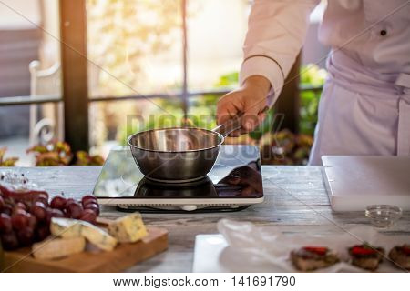 Fire in saucepan. Man's hand holding pan. Work in the kitchen. Preparing sauce for meat.