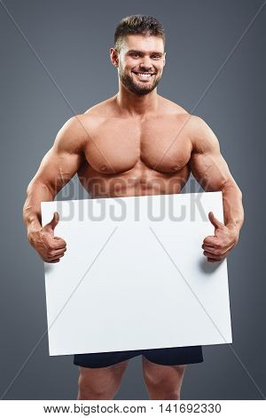 Smiling naked muscular man covering with a white banner isolated over grey background. Vertical portrait of fitness man holding a white paper and showing thumbs up with copy space