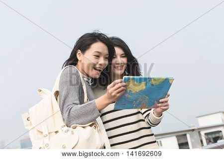 Asian young girl travel and look the map at Victoria Harbor, Hong Kong, Asia