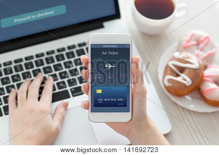 female hands holding white phone with online air ticket in the screen on table with laptop