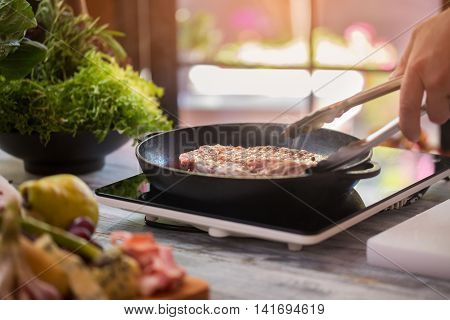 Meat on frying pan. Hand of man with tongs. Appetizing smell of beef. Steak cooked at special recipe.