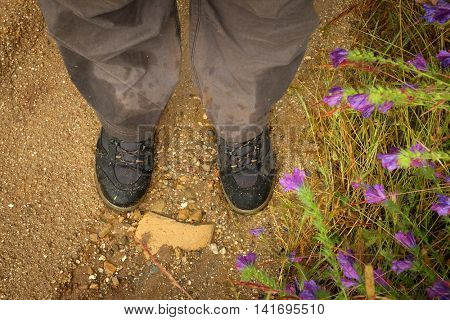 Detail of wet trousers and muddy trekking boots in a dirt trail