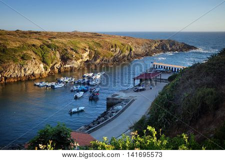 Groups of boats anchored in a calm bay in Porto Covo town, Portugal