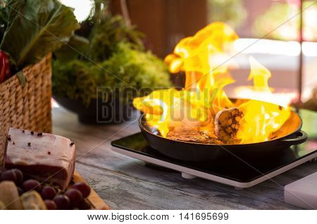 Flame in black pan. Piece of meat in fire. Chef's secret for preparing steak. Situation is under control.